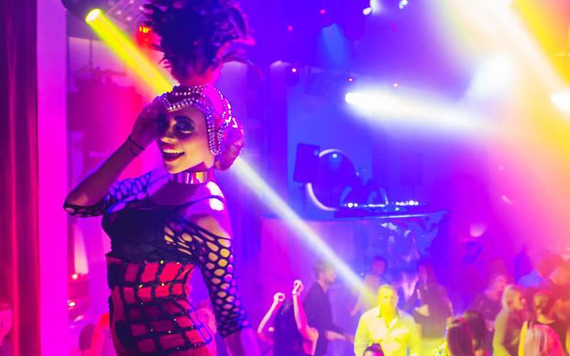 A woman dressed up in a club with a feather plume on her headdress