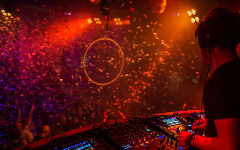 A DJ performing to a crowd, with confetti falling over them