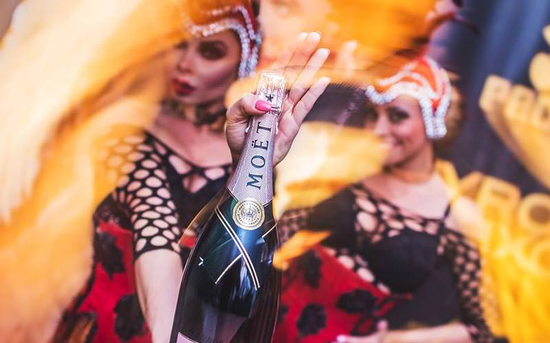 Two women dressed up, whilst one holds a bottle of Moet