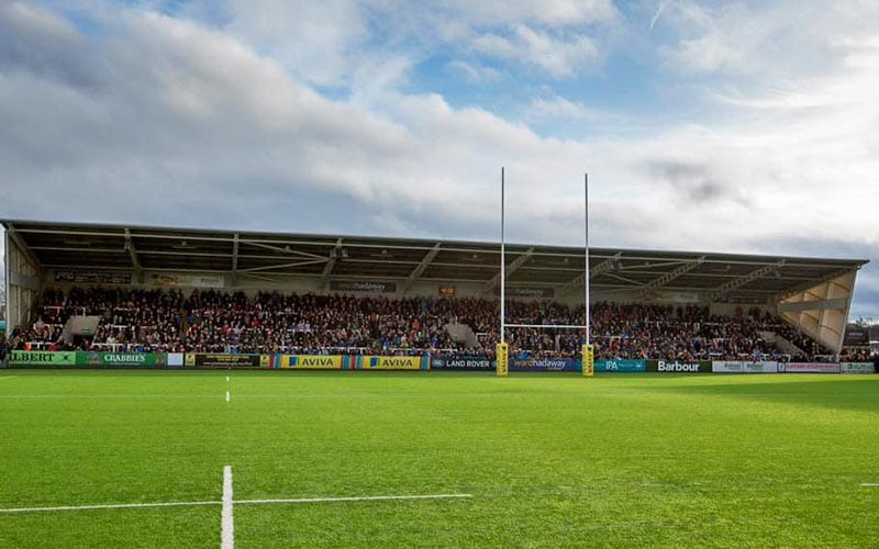 Image of Kingston park pitch with posts and filled stand in the background.