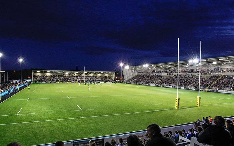 Night image of Kingston Park on matchday with floodlights on and stands filled.