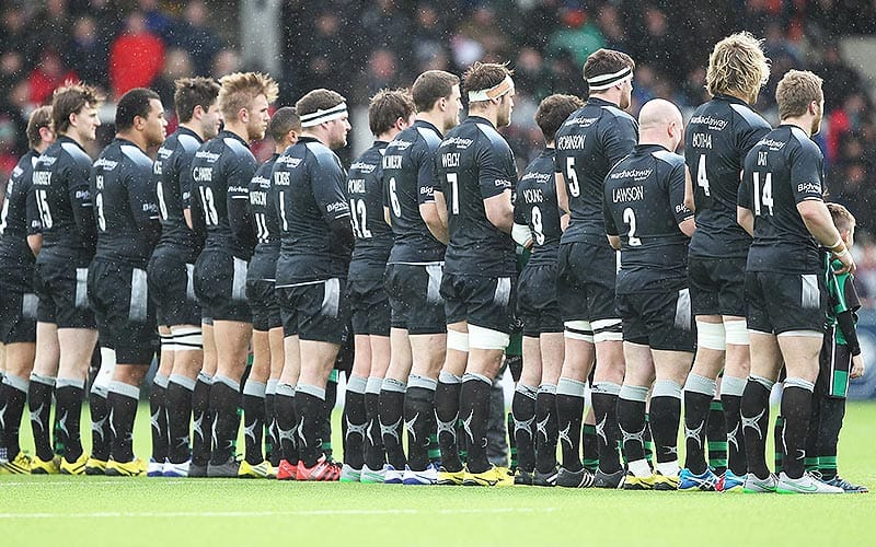 Image of the back of Newcastle Falcons team lined up at the start of a match.