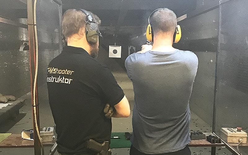 A man learning to shoot with an instructor