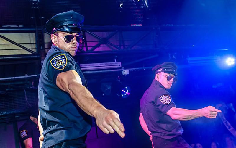 Two male strippers performing, dressed as policemen