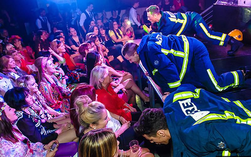 Male strippers dressed as firemen, crawling on stage facing audience of smiling women