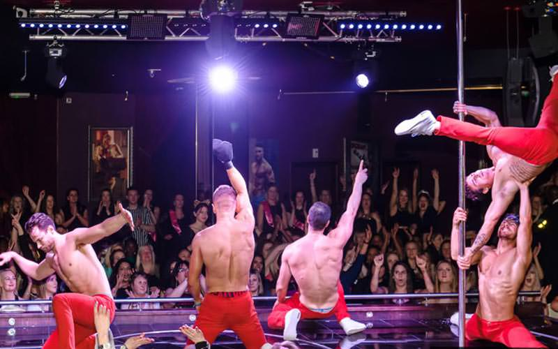 5 male strippers on a central stage wearing karate style clothing