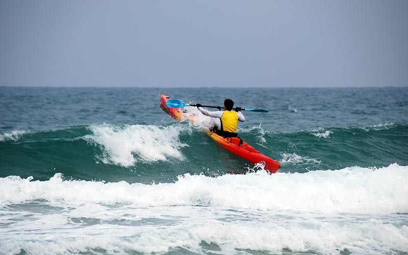 A man heading out to sea on a kayak