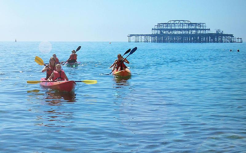 Some women in kayaks on the sea with a pier in the background