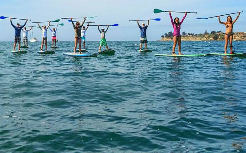 Women standing on their kayaks with their oars in the air