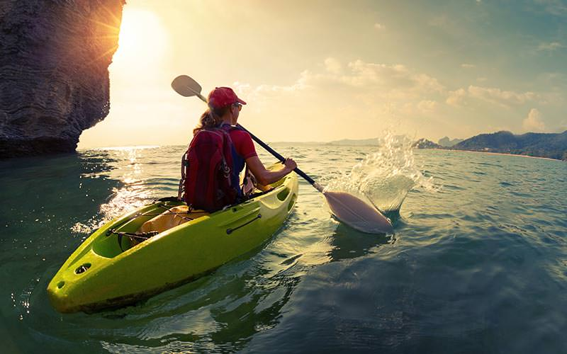 A woman heading out to sea in a kayak