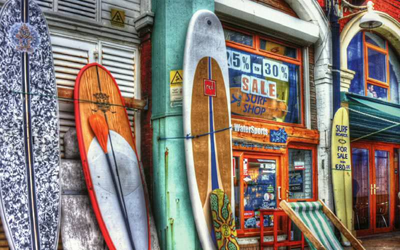 Some surfboards up against a wall in a street