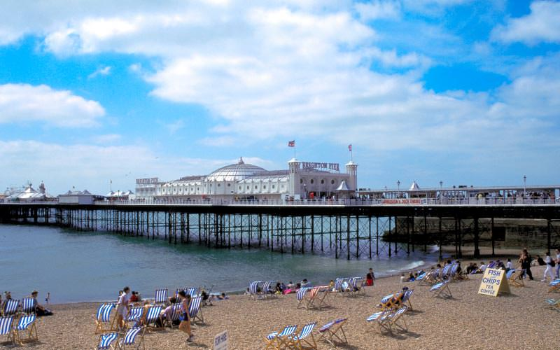 A beach with people on, and the pier in the background
