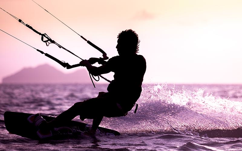 A man wakeboarding on the sea and holding on to a harness