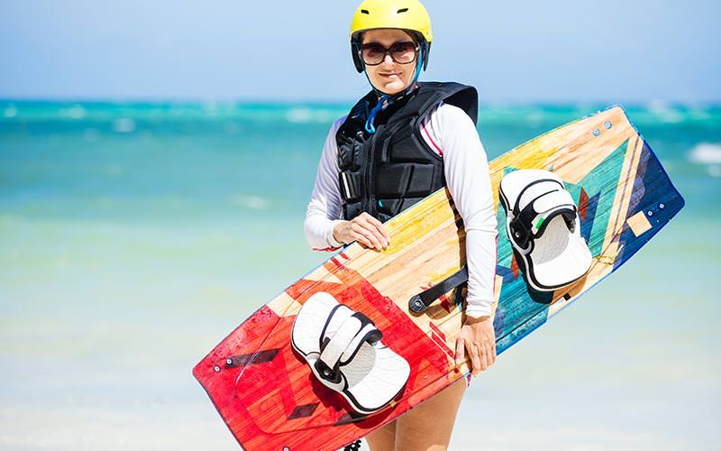 A woman holding a wakeboard on the beach