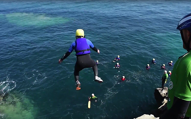 Someone jumping off a cliff into water whilst an instructor looks on