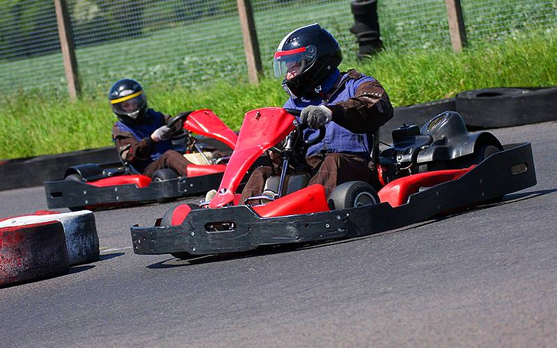 Two people driving karts on an outdoor track