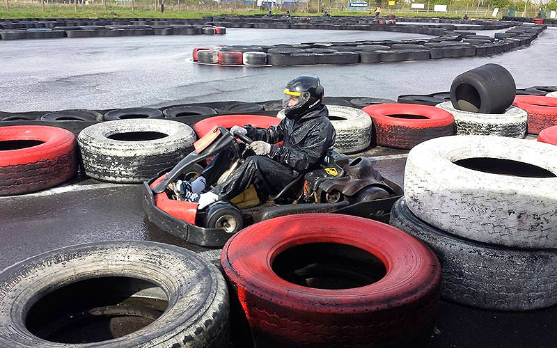 A man driving a kart on an outdoor track, lined with tyres