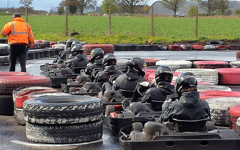 People lined up in go karts on an outdoor track