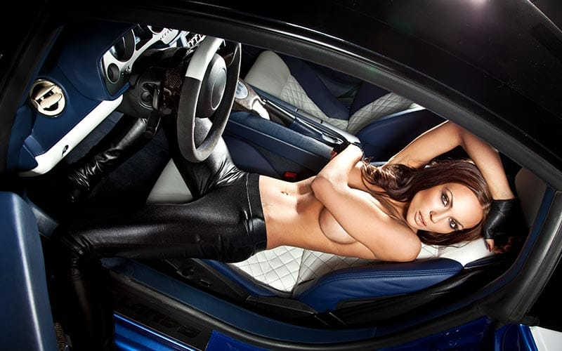 A girl lying in the driving seat of a car with no top on