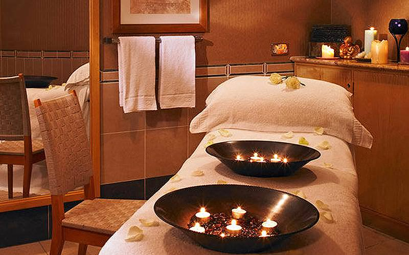 Candles in two silver bowls on top of a treatment bed in a beauty room