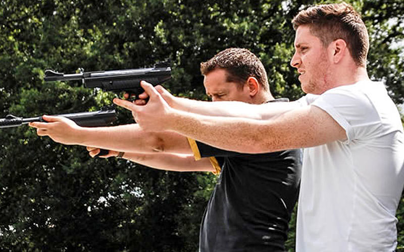 Two men aiming with air pistols