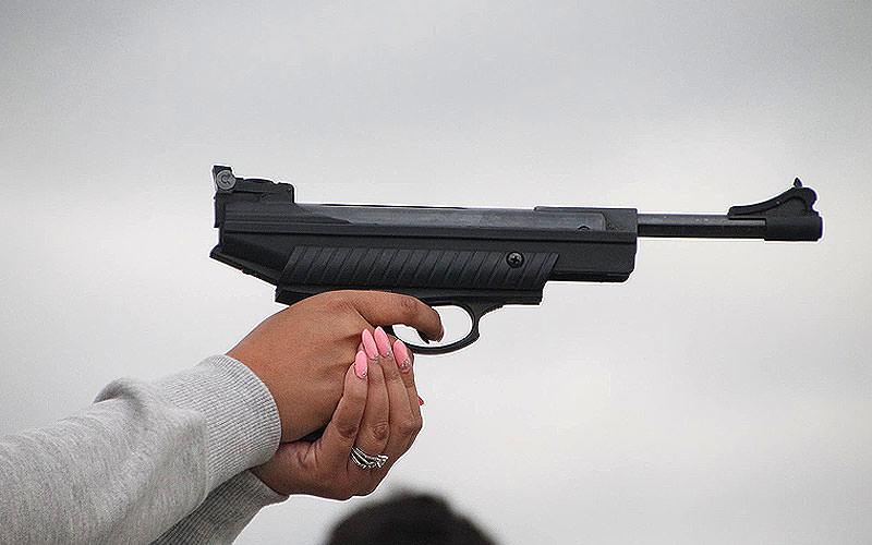 Close up of a woman holding an air pistol