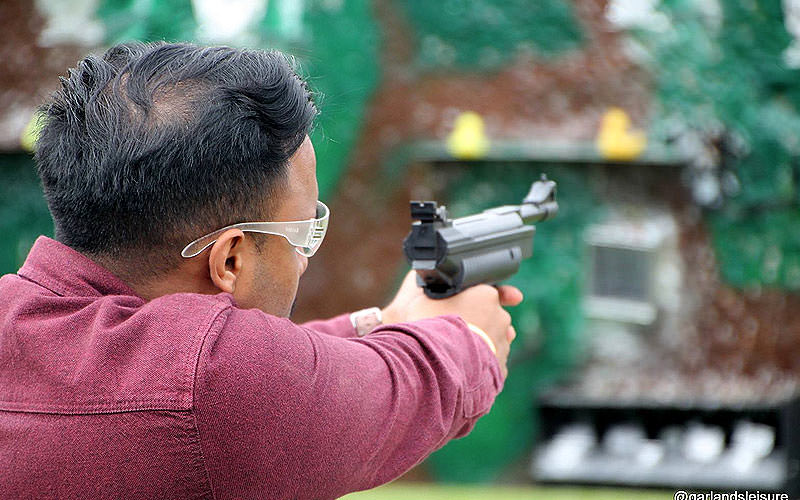 Back shot of a man aiming with an air pistol