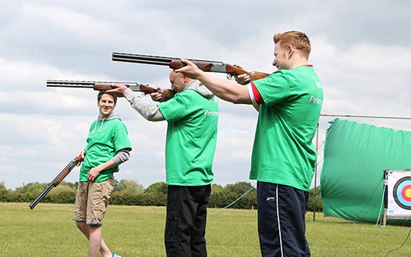 Three people aiming with shotguns