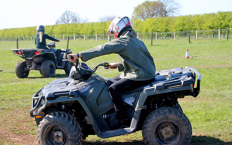 A man driving a quad bike in a field, with a woman driving one in the background