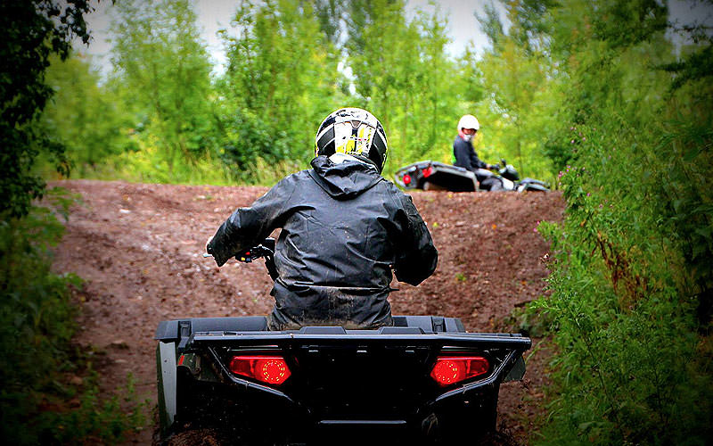 The back of a man driving a quad bike on a muddy path, with another man waiting in the foreground