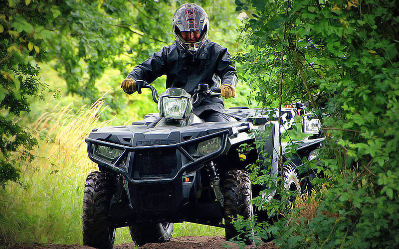 A man driving a quad bike on a muddy path