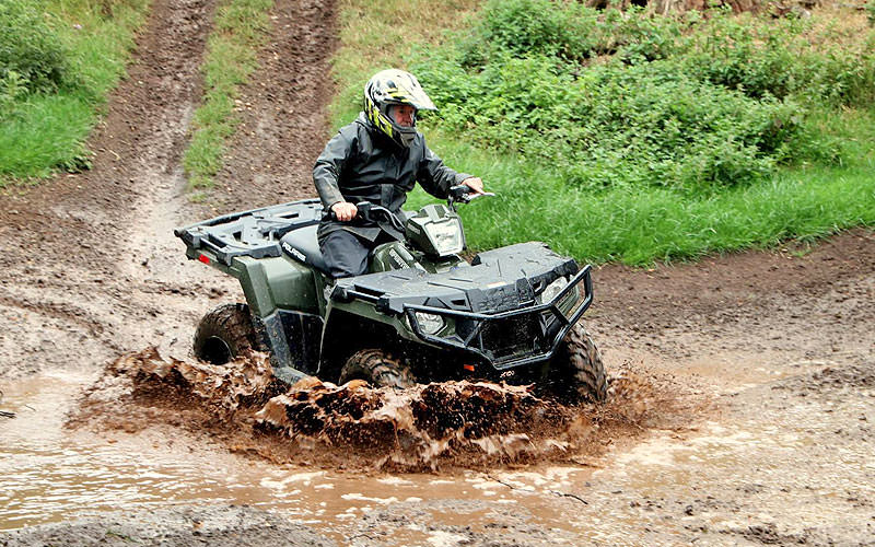 A man driving a quad bike through a muddy puddle