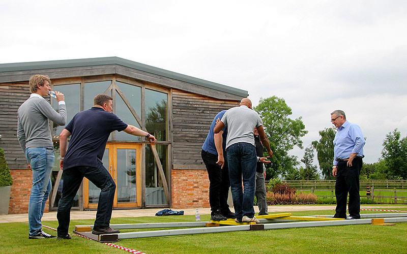 Some men participating in outdoor bridge building activity