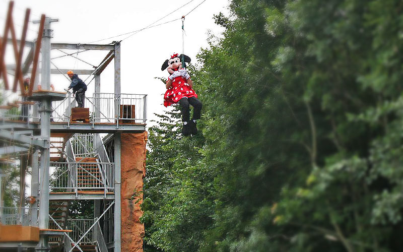 A person dressed as Minnie Mouse, jumping off a zipline