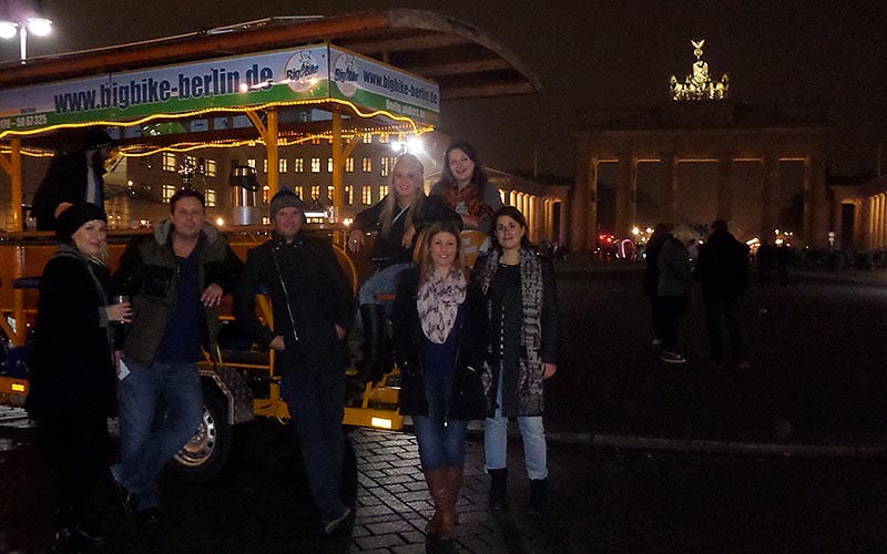 Image of a group of people standing beside a beer bike
