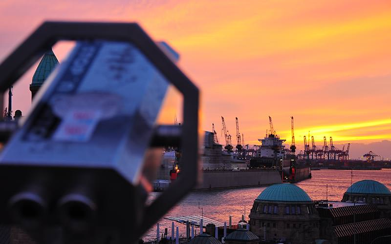 View of Hamburg harbour at sunset with a telescope in the foreground