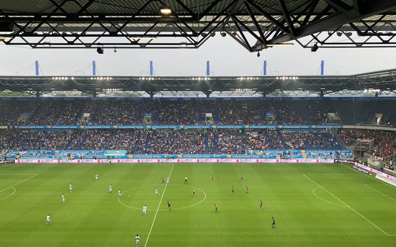 Image of the stadium filled with crowds of people watching the footballers on the pitch