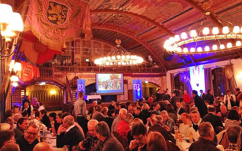 People sat on long benches inside the Hofbrauhaus