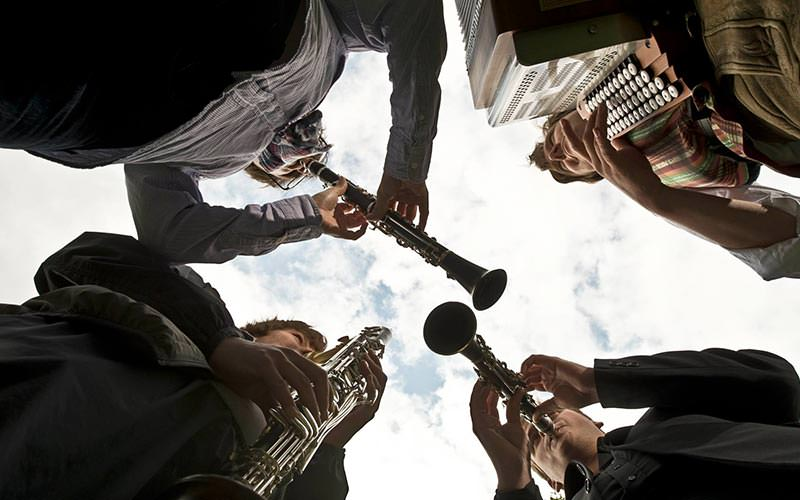 Camera shot looking up at an Oompah band playing instruments in a circle