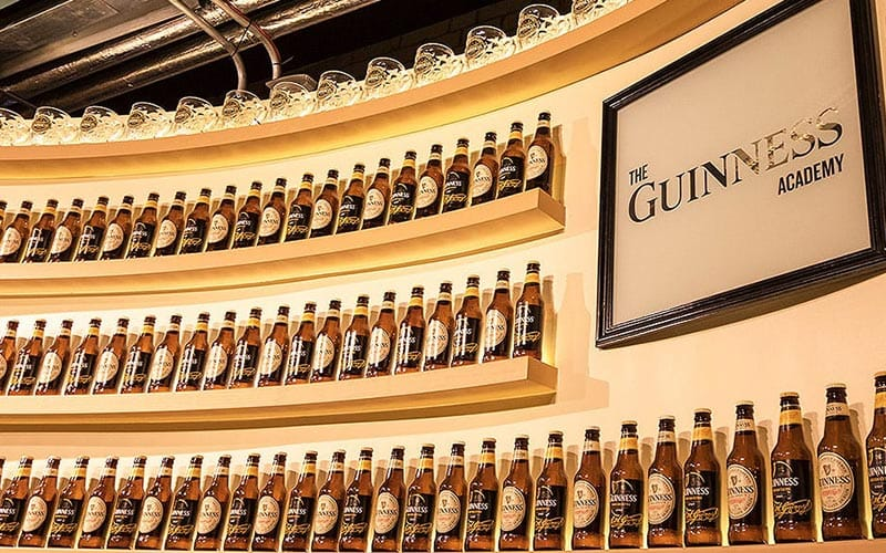 Bottles of Guinness lined up on the semi-circular wall in The Guinness Academy