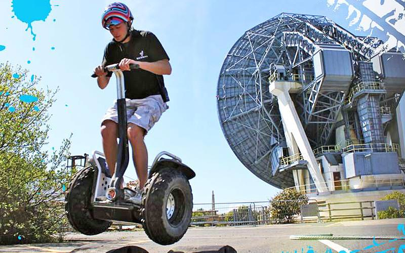 A man riding a Segway in front of a giant building
