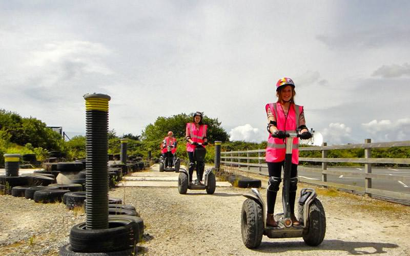A line of women in pink hi vis, riding Segways outdoors