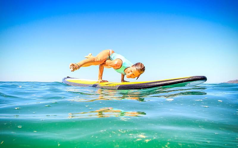 A woman balancing on her hands with her legs in the air on a paddle board