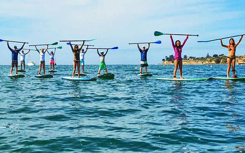People stood on paddle boards and holding up their oars