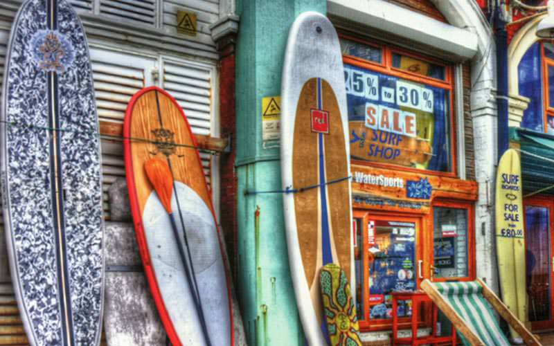 Paddle boards lined up on the outside of a surf shop