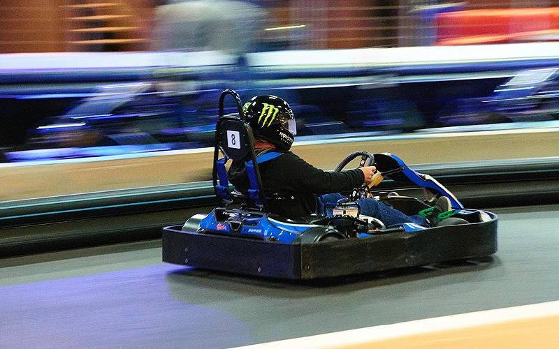 A man in a Go-Kart driving at speed on an indoor track