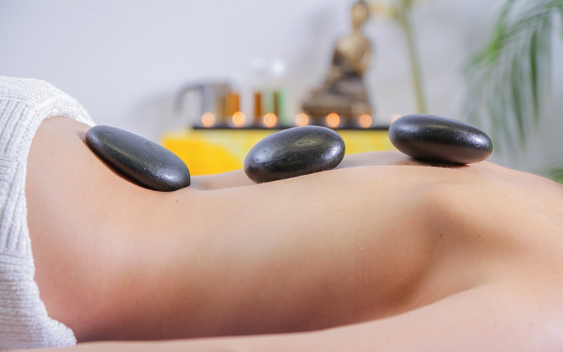 A woman lying on a bed with hot stones on her back