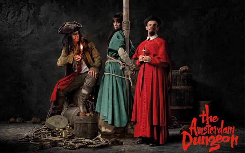 Two men in period costumes, with a women in a costume tied to a wooden pole