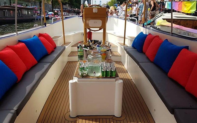A close up of seating and a table with alcohol on it on a boat