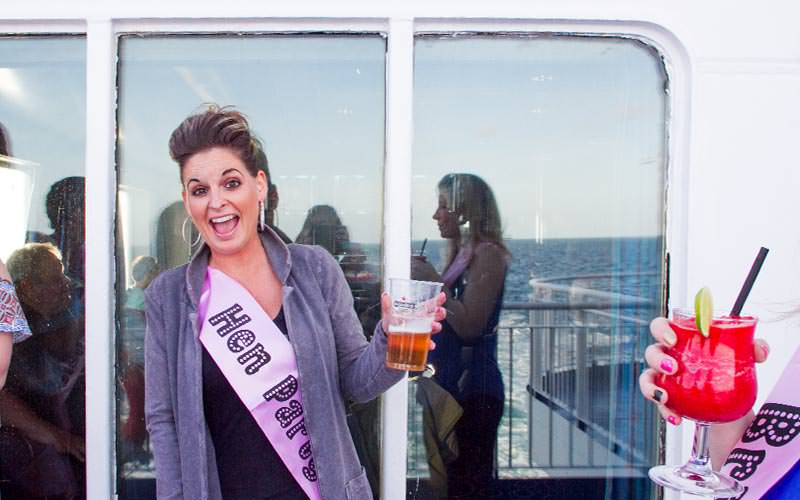 A woman in a pink hen party sash, posing whilst holding a beer on the deck of a boat